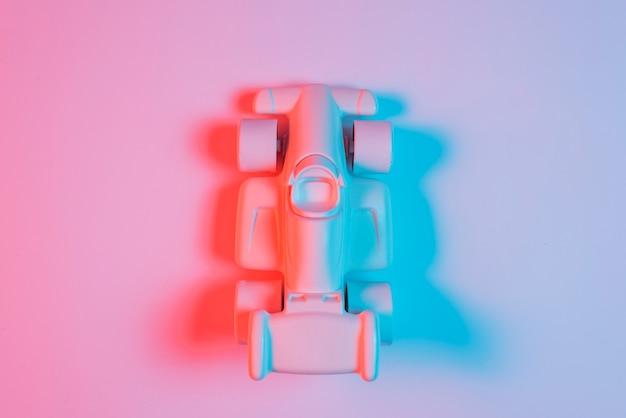 Punto di vista dell'angolo alto di piccola automobile sportiva con ombra e luce blu sul contesto