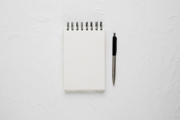 Punto di vista dell'angolo alto di un blocco note a spirale in bianco bianco con la penna a sfera