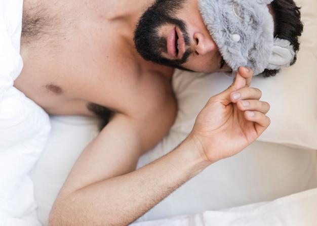 Punto di vista dell'angolo alto di un uomo senza camicia che dorme sul letto con una maschera per gli occhi