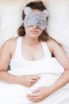 Punto di vista dell'angolo alto di una donna che dorme con una maschera di occhio
