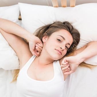 Punto di vista dell'angolo alto di una giovane donna che sveglia sul letto