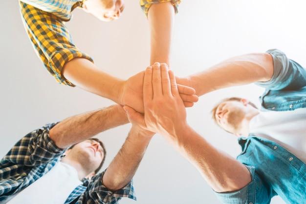 Punto di vista di angolo basso degli amici maschii che impilano le mani contro il fondo bianco