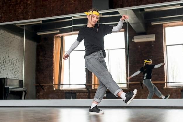 Punto di vista di angolo basso del ballerino femminile che balla nello studio