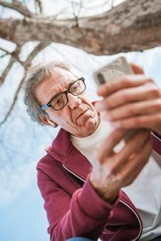 Punto di vista di angolo basso dell'uomo senior serio che per mezzo dello smart phone