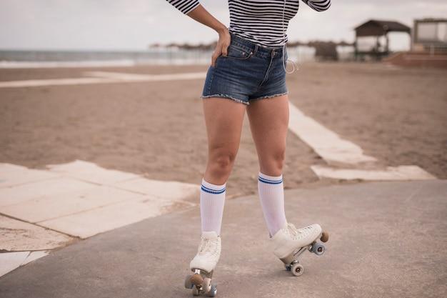 Punto di vista di angolo basso della donna che equilibra sul pattino a rotelle alla spiaggia