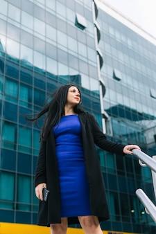 Punto di vista di angolo basso della donna di affari che sta davanti all'edificio per uffici