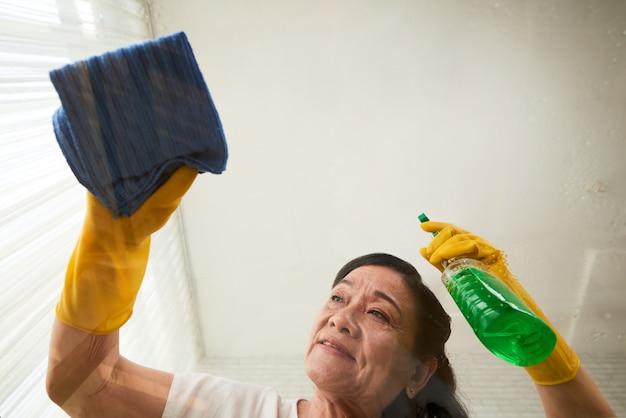 Punto di vista di angolo basso della donna senior che pulisce la tavola di vetro con spruzzo