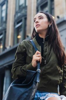 Punto di vista di angolo basso della giovane donna che tiene borsa blu che cammina nella via