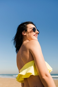 Punto di vista di angolo basso della giovane donna sorridente in bikini che sta contro il chiaro cielo alla spiaggia