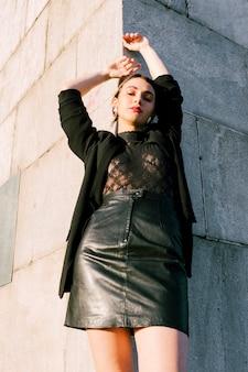 Punto di vista di angolo basso di giovane donna alla moda che si appoggia la parete con la sua mano sollevata