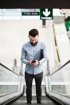 Punto di vista di angolo basso di giovane uomo d'affari che sta sulla scala mobile per mezzo del telefono cellulare