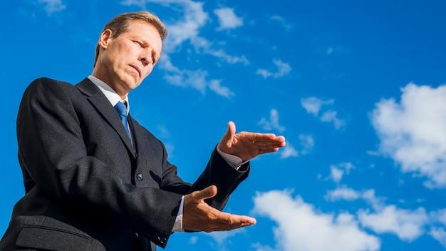 Punto di vista di angolo basso di un uomo d'affari che presenta qualcosa contro il cielo blu