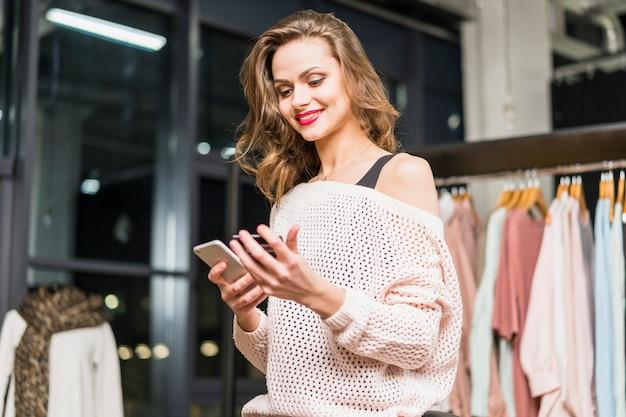 Punto di vista di angolo basso di una giovane donna alla moda che per mezzo del cellulare e della carta di regalo per l'acquisto online