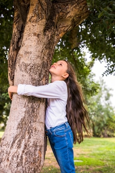 Punto di vista di angolo basso di una ragazza con i capelli lunghi che abbracciano albero