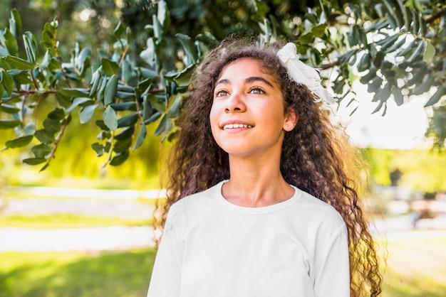 Punto di vista di angolo basso di una ragazza felice che sta nel parco