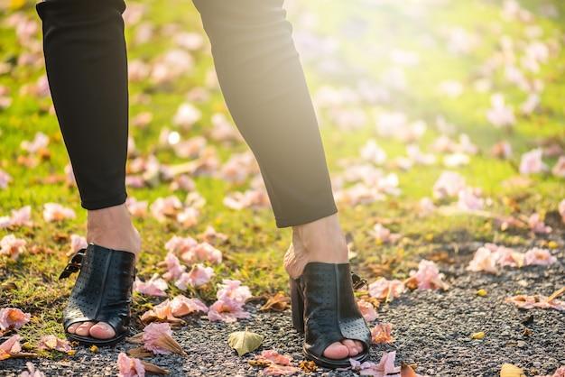 Punto di vista di gambe di una donna che cammina con i fiori. gambe asiatiche della donna