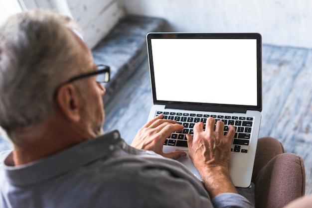 Punto di vista elevato dell'uomo che per mezzo del computer portatile con lo schermo in bianco bianco
