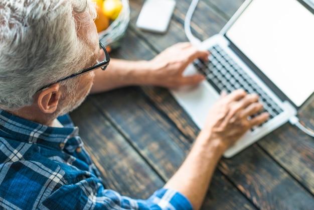 Punto di vista elevato dell'uomo senior che scrive sul computer portatile sopra lo scrittorio di legno