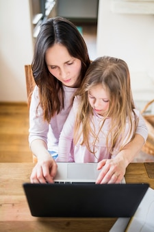 Punto di vista elevato della donna con sua figlia che per mezzo del computer portatile sullo scrittorio di legno