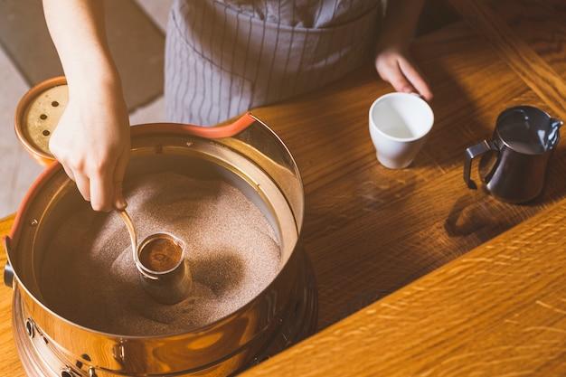 Punto di vista elevato della mano femminile che produce caffè turco sulla sabbia nel caf�