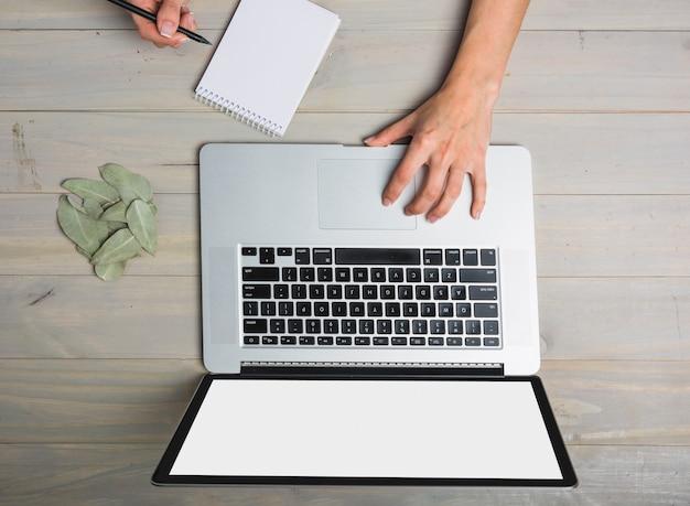 Punto di vista elevato della persona di affari che per mezzo del computer portatile mentre scrivendo sul blocco note