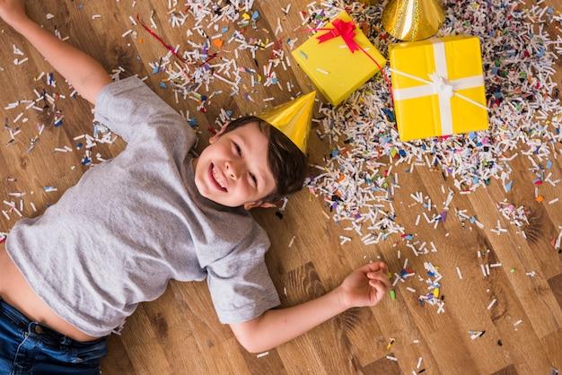 Punto di vista elevato di un ragazzo felice che si trova sul pavimento di legno duro con i coriandoli; scatole regalo e cappello da festa