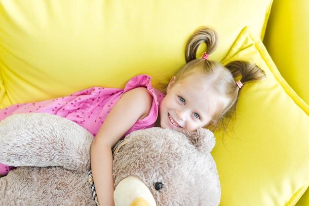 Punto di vista elevato di una bambina sveglia che abbraccia il suo orsacchiotto