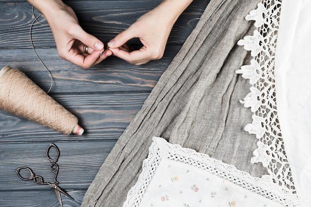 Punto di vista elevato di una donna che inserisce filo nell'ago vicino ai tessuti sopra il tavolo in legno
