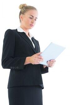 Punto di vista laterale di angolo basso della giovane donna bionda che per mezzo della sua compressa