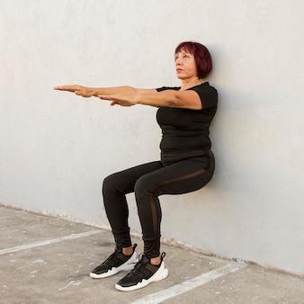 Punto di vista lungo della donna che fa esercizio del supporto della parete
