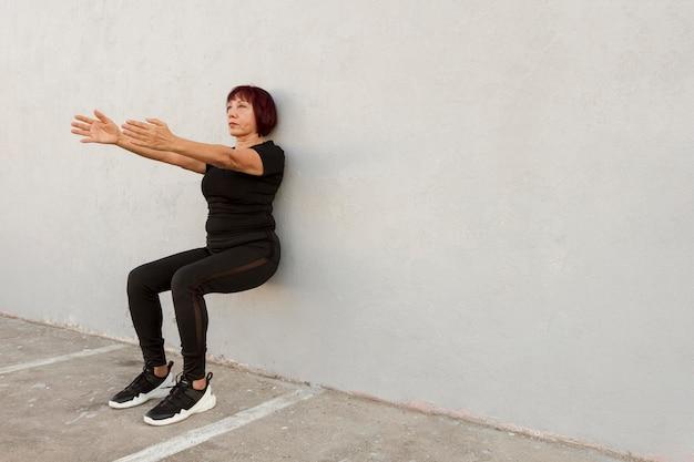 Punto di vista lungo della donna che fa lo spazio della copia di esercizio del supporto della parete