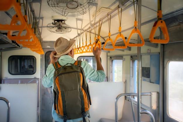 Punto di vista posteriore dei viaggiatori con zaino e sacco a pelo asiatici che tengono corrimano dentro il treno pubblico in vacanza