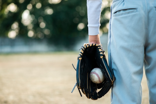 Punto di vista posteriore del baseball della tenuta dell'uomo in guanto