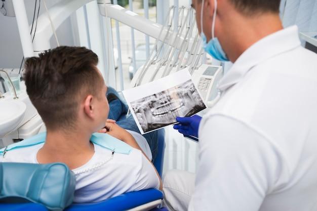 Punto di vista posteriore del dentista che mostra radiografia al paziente