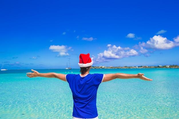 Punto di vista posteriore del giovane in cappello di santa sulla spiaggia tropicale
