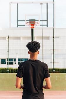 Punto di vista posteriore del maschio anonimo atletico al campo da pallacanestro