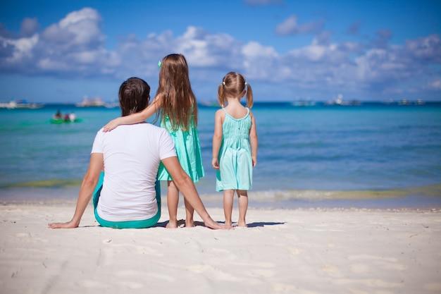 Punto di vista posteriore del padre felice con le sue due figlie in vacanza spiaggia tropicale