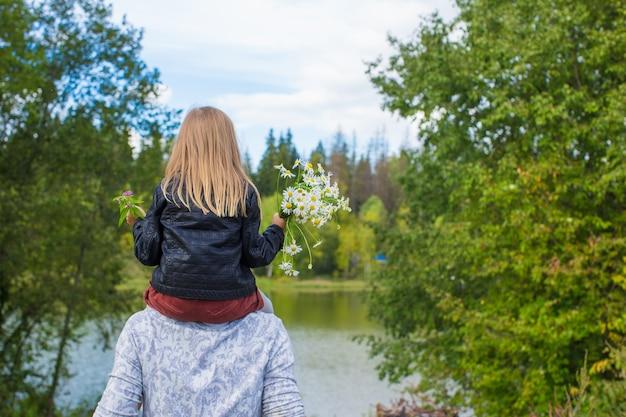 Punto di vista posteriore del padre felice e della piccola figlia nel parco