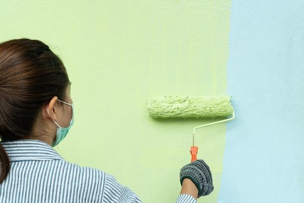 Punto di vista posteriore del pittore della giovane donna in camicia e guanti che dipingono una parete con il rullo di pittura.