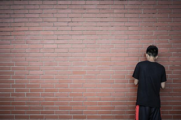 Punto di vista posteriore del ragazzo asiatico adolescente che sta davanti al fondo rosso del muro di mattoni