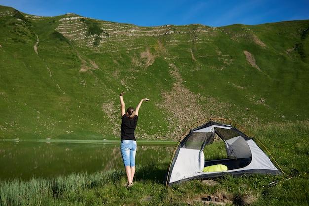 Punto di vista posteriore del turista della giovane donna, stante con le mani di sollevamento su nell'aria vicino alla tenda, godendo della giornata di sole vicino al lago nelle montagne. vacanze estive di avventura di concetto di stile di vita all'aperto