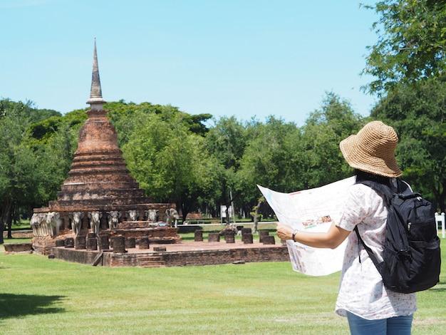 Punto di vista posteriore del viaggiatore con zaino e sacco a pelo asiatico della donna che esamina la mappa il vecchio tempio