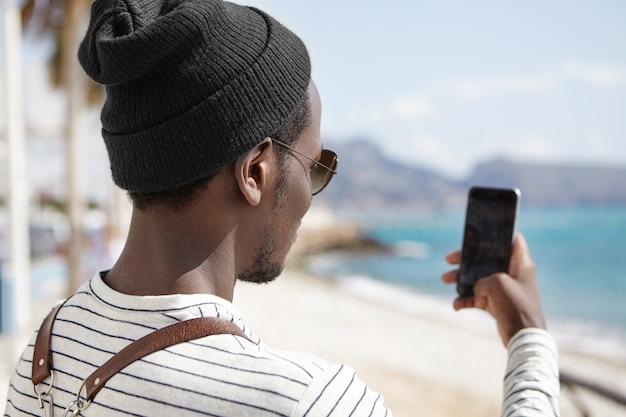 Punto di vista posteriore del viaggiatore con zaino e sacco a pelo nero in cappello e camicia a strisce di fronte al mare, tenendo smartphone e scattare foto del bellissimo paesaggio durante il suo viaggio
