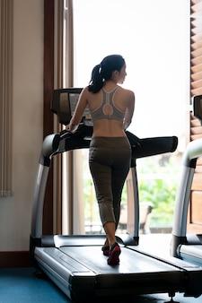Punto di vista posteriore dell'atleta della giovane donna che corre sulla pedana mobile in palestra