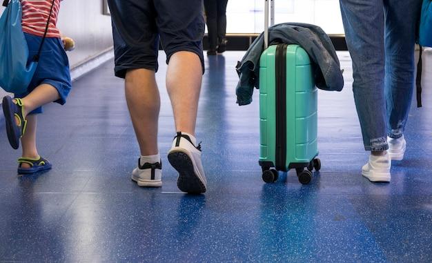 Punto di vista posteriore dell'uomo che cammina con la valigia