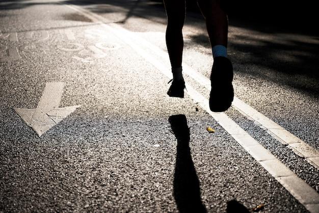 Punto di vista posteriore dell'uomo che corre sulla strada
