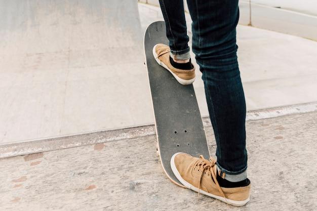Punto di vista posteriore dell'uomo che equilibra sullo skateboard