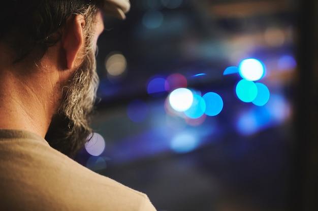 Punto di vista posteriore dell'uomo che guarda fuori dalla finestra con le luci di emergenza sfocate