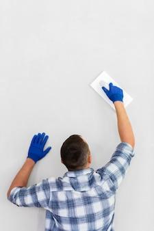 Punto di vista posteriore dell'uomo che lavora alla parete con lo spazio della copia