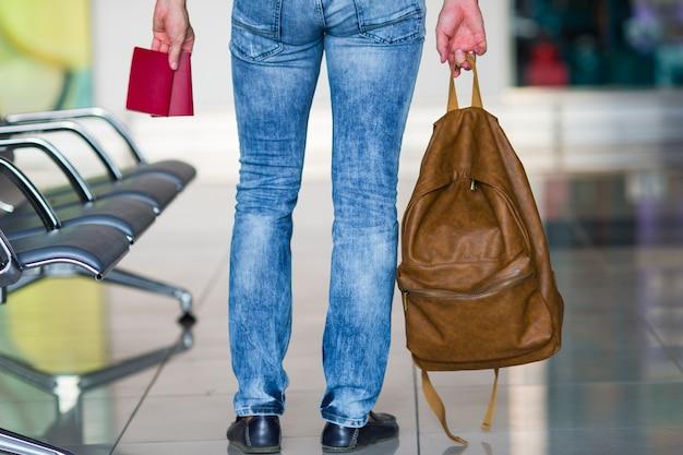 Punto di vista posteriore dell'uomo con i passaporti e lo zaino in mani all'aeroporto